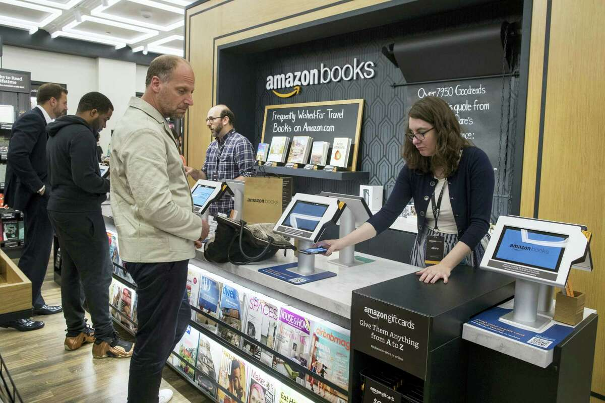 In this May 25, 2017, photo, a salesperson helps a customer use his smartphone to make a payment at the Amazon Books store in the Time Warner Center at Columbus Circle, in New York. Amazon, the e-commerce giant that changed how people shop for books, toilet paper and TVs, hit a new milestone Tuesday, May 30: Its stock topped $1,000 for the first time.