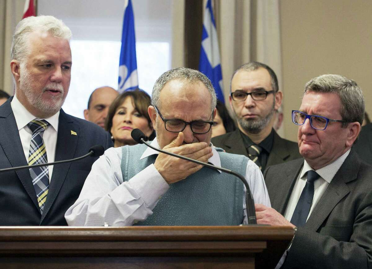 CORRECTS NAME AND TITLE TO LABIDI FROM LABIBI AND VICE PRESIDENT FROM PRESIDENT - Mohamed Labidi, the vice-president of the mosque where an attack happened, is comforted by Quebec Premier Philippe Couillard, left, and Quebec City mayor Regis Labeaume, right, during a news conference Monday about the fatal shooting at the Quebec Islamic Cultural Centre on Sunday. Prime Minister Justin Trudeau and Couillard both characterized the attack at the mosque during evening prayers as a terrorist act.