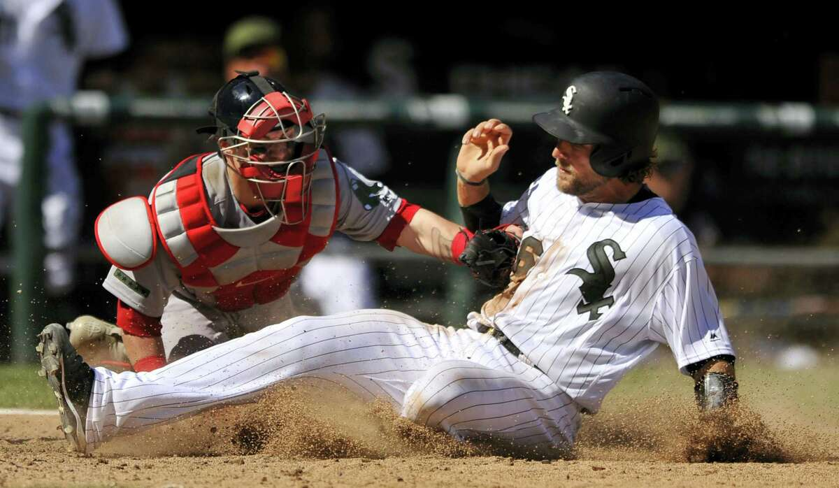 Chicago White Sox's Kevan Smith, right, slides safely into home plate on a Melky Cabrera single while Boston Red Sox catcher Christian Vazquez tries to apply the tag during the seventh inning of Chicago's. 5-4 win.
