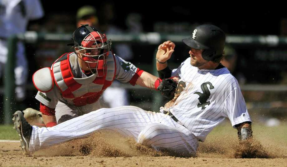 Chicago White Sox's Kevan Smith, right, slides safely into home plate on a Melky Cabrera single while Boston Red Sox catcher Christian Vazquez tries to apply the tag during the seventh inning of Chicago's. 5-4 win. Photo: PAUL BEATY - THE ASSOCIATED PRESS  / FR36811 AP