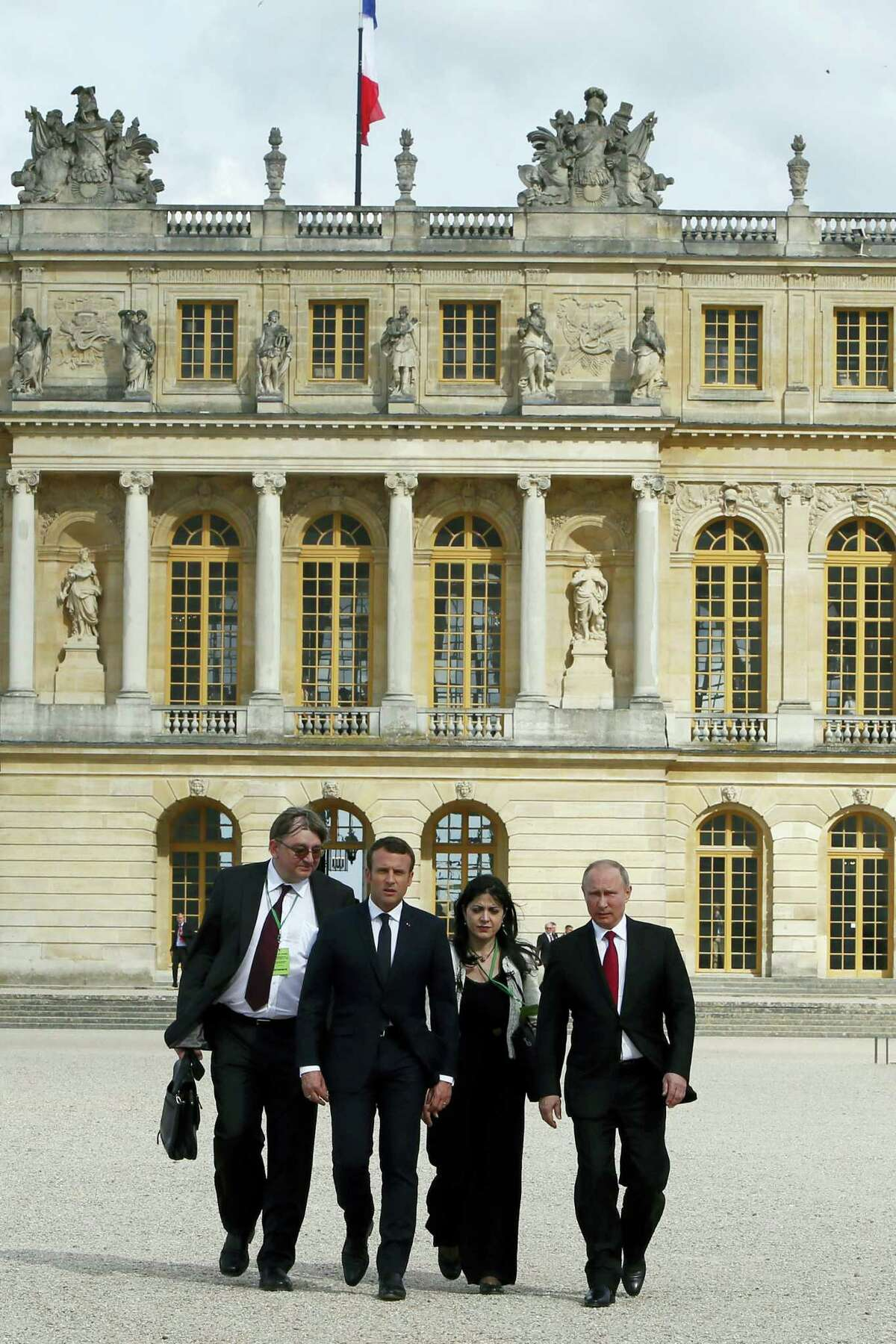 French President Emmanuel Macron, second left, and Russian President Vladimir Putin, right, followed by their interpreters, walk in the garden of the Versailles Palace following their meeting in Versailles, near Paris, France, Monday, May 29, 2017. Monday's meeting comes in the wake of the Group of Seven's summit over the weekend where relations with Russia were part of the agenda, making Macron the first Western leader to speak to Putin after the talks.
