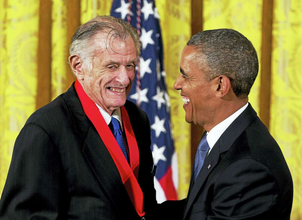 """In this July 10, 2013, file photo, President Barack Obama laughs with Frank Deford as he awards him the 2012 National Humanities Medal during a ceremony in the East Room of White House in Washington. Deford gave his final sports commentary on NPR's """"Morning Edition"""" Wednesday, ending a run of what he calls """"little homilies"""" that began in 1980."""