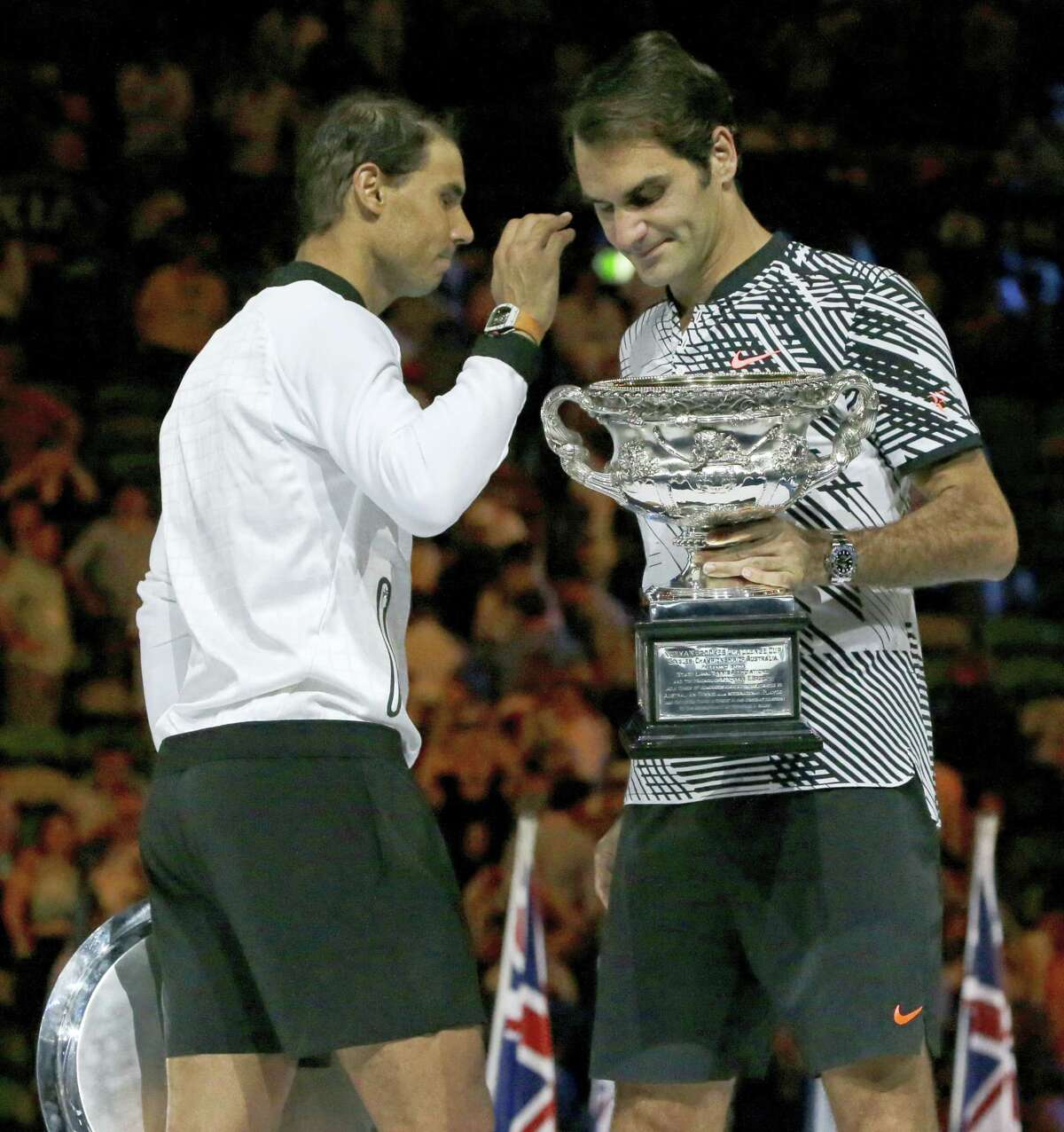 Switzerland's Roger Federer, right, holds his trophy after defeating Spain's Rafael Nadal, left, during their men's singles final at the Australian Open tennis championships in Melbourne, Australia, Sunday.