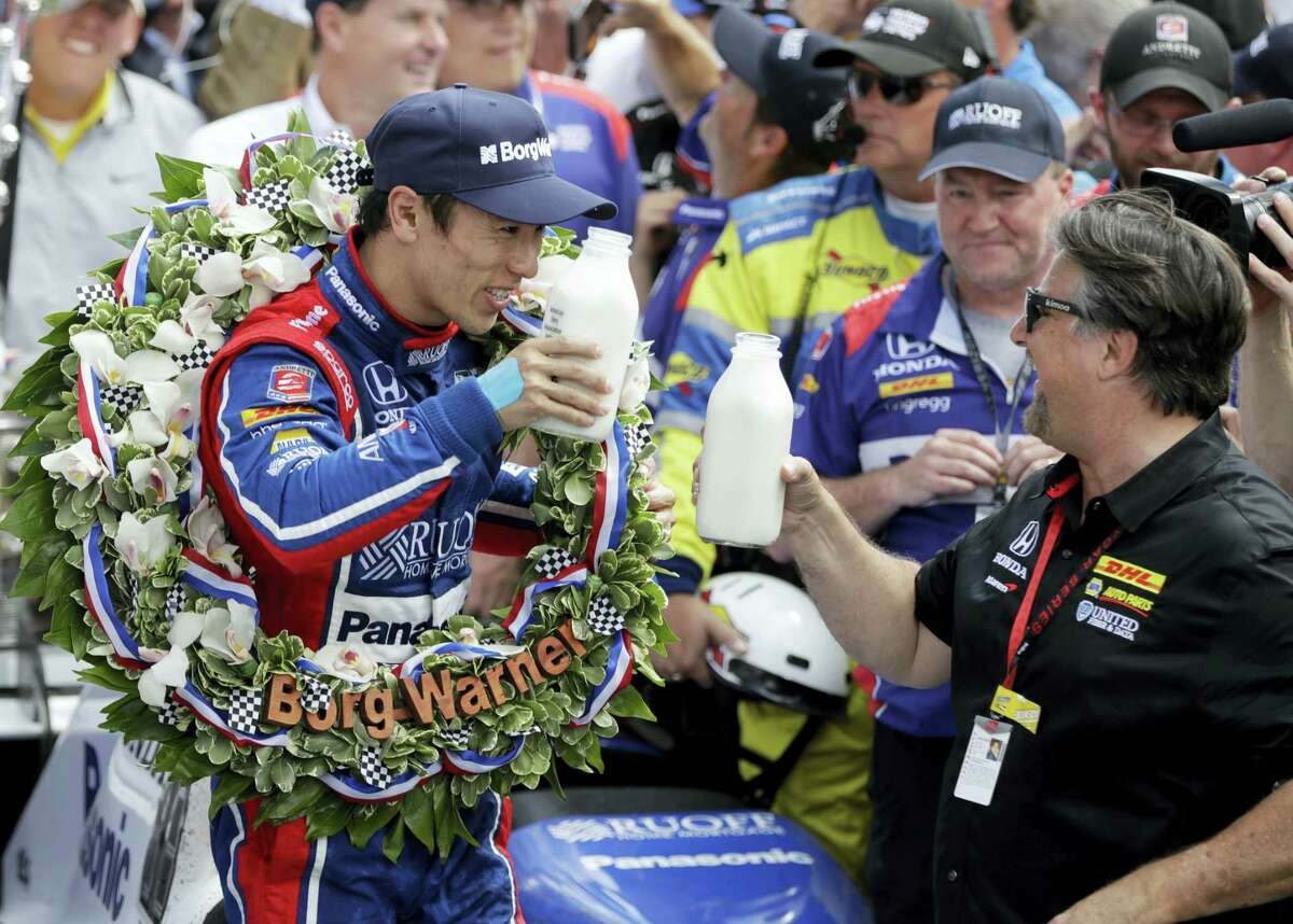 Takuma Sato, left, toasts with car owner Michael Andretti as they celebrate after winning the Indianapolis 500 on Sunday.