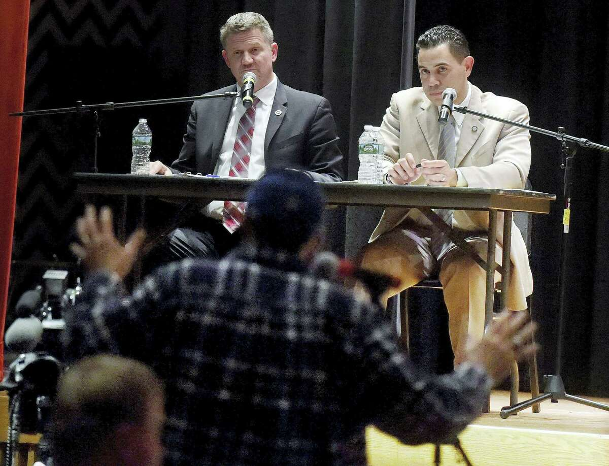 In this Thursday photo, Mohegan Tribal Council Chairman Kevin Brown, left rear, and Mashantucket Pequot Tribal Council Chairman Rodney Butler, right rear, listen as Mike Russo, foreground, voices opposition to a proposed casino during a public hearing in Windsor Locks, Conn. The tribes seek approval from the General Assembly to build a jointly owned casino in either East Windsor or Windsor Locks to help compete with the MGM Resorts International casino under construction in Springfield, Mass.
