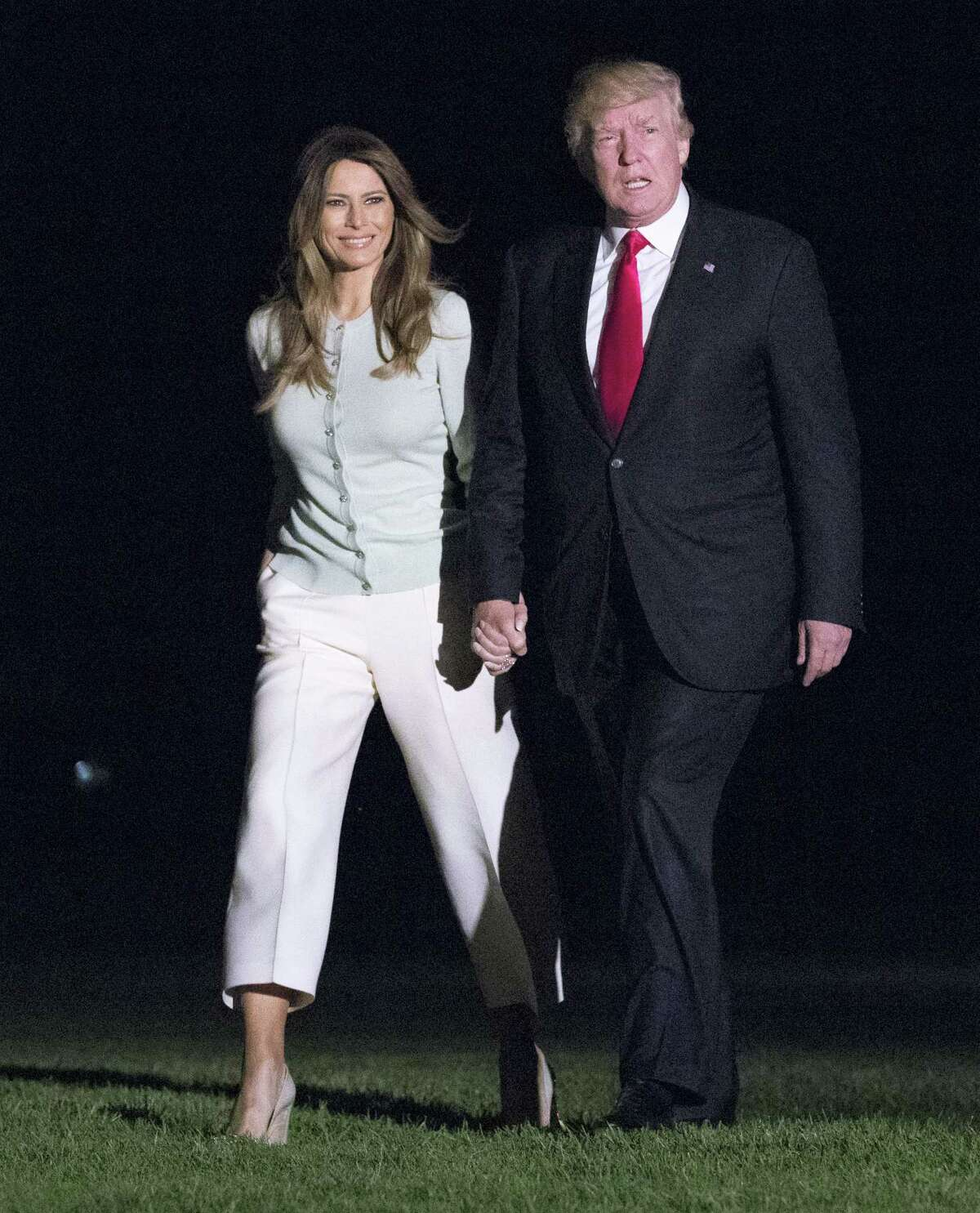 President Donald Trump and first lady Melania Trump walk from Marine One across the South Lawn to White House in Washington on May 27, 2017 as they return from Sigonella, Italy.