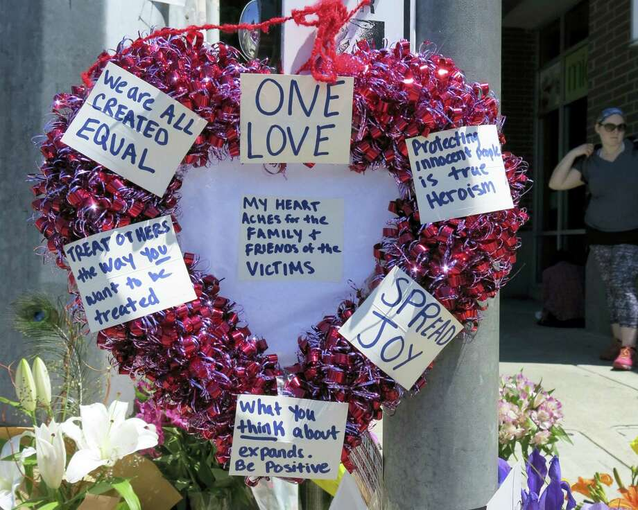 A heart-shaped wreath covered with positive messages hangs on a traffic light pole at a memorial for two bystanders who were stabbed to death Friday, while trying to stop a man who was yelling anti-Muslim slurs and acting aggressively toward two young women, including one wearing a Muslim head covering, on a light-trail train in Portland, Ore, Saturday, May 27, 2017. A memorial grew all day Saturday outside the transit center in Portland, as people stopped with flowers, candles, signs and painted rocks. Jeremy Joseph Christian, 35, was booked on suspicion of murder and attempted murder in the attack. (AP Photo/Gillian Flaccus) Photo: AP / Copyright 2017 The Associated Press. All rights reserved.