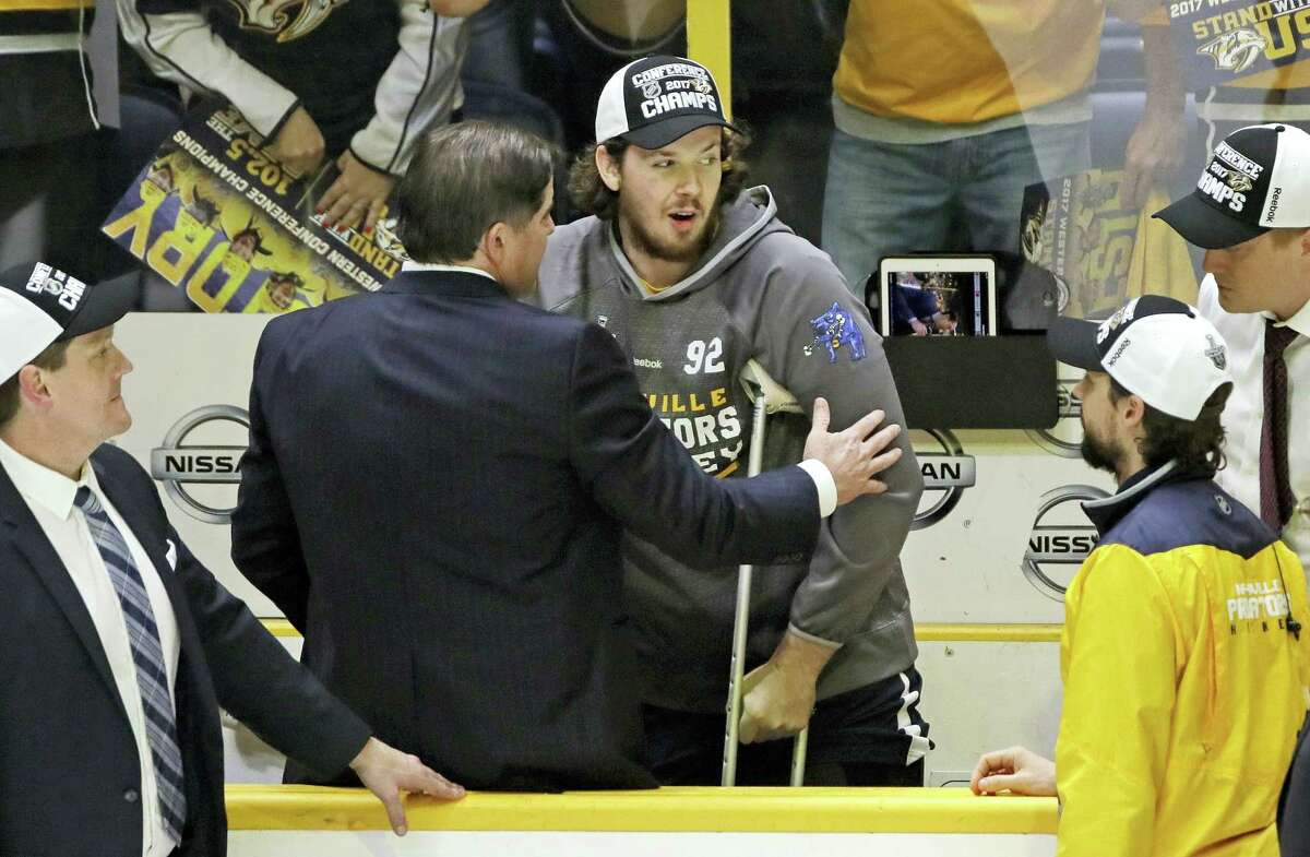 Injured Predators center Ryan Johansen, center, celebrates with coach Peter Laviolette after the Predators beat the Ducks in the Western Conference final.