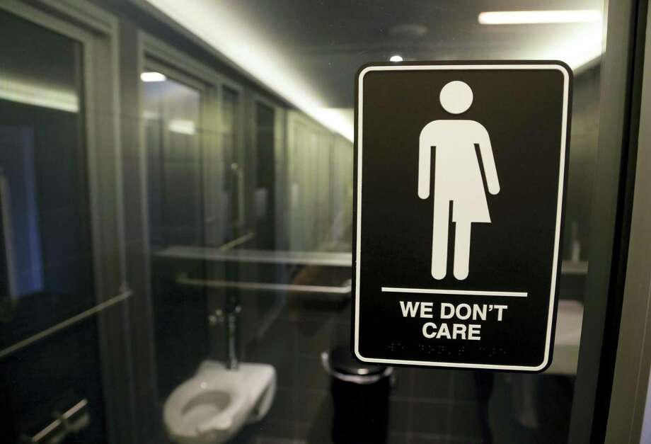 """This May 12, 2016 photo shows a sign outside a restroom at 21c Museum Hotel in Durham, N.C. The Associated Press has determined that North Carolina's law limiting LGBT protections will cost the state more than $3 billion in lost business over a dozen years.That's despite Republican assurances that the """"bathroom bill"""" isn't hurting the economy. Photo: AP Photo — Gerry Broome, File  / Copyright 2017 The Associated Press. All rights reserved."""