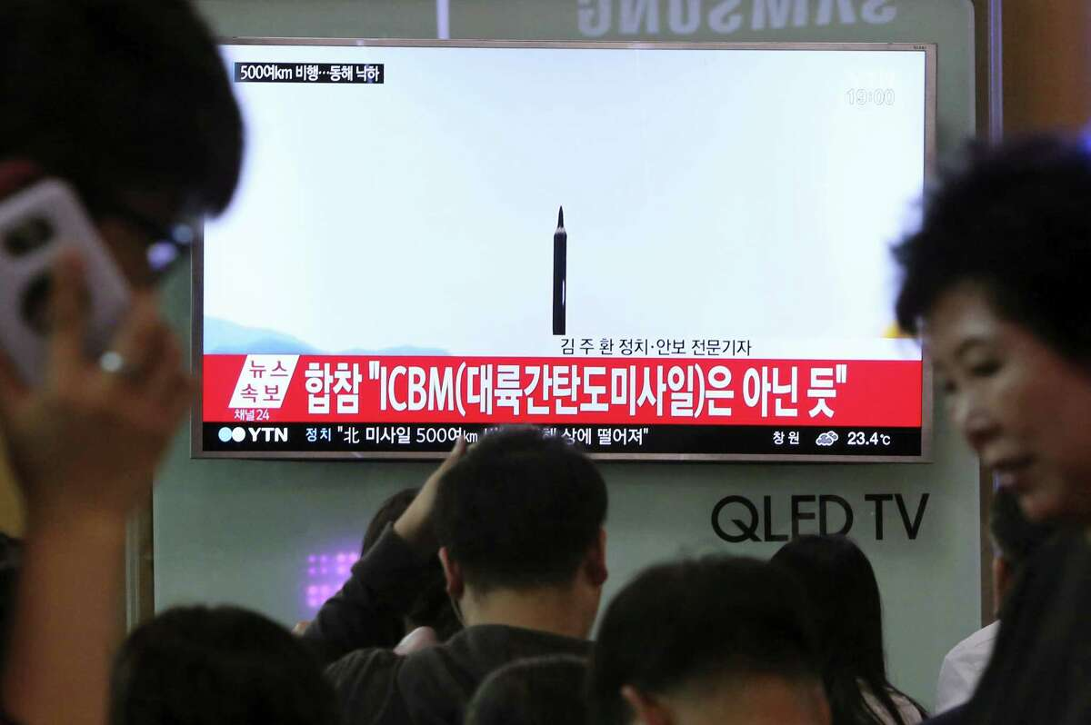 In this May 21, 2107, file photo people watch a TV news program showing a file image of a missile launch conducted by North Korea, at the Seoul Railway Station in Seoul, South Korea. With North Korea's nuclear missile threat in mind, the Pentagon is planning a missile defense test next week that for the first time will target an intercontinental-range missile.