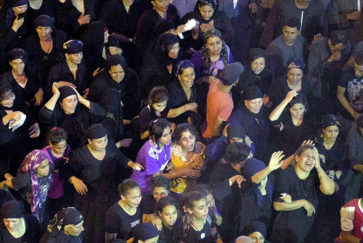 Relatives of Coptic Christians killed in a bus attack react during their funeral service at Abu Garnous Cathedral in Minya, Egypt, Friday, May 26, 2017. Egyptian security and medical officials say the death toll in the shooting by masked gunmen of a bus carrying Christians, many of them children, on their way to a remote desert monastery has risen to over 29.