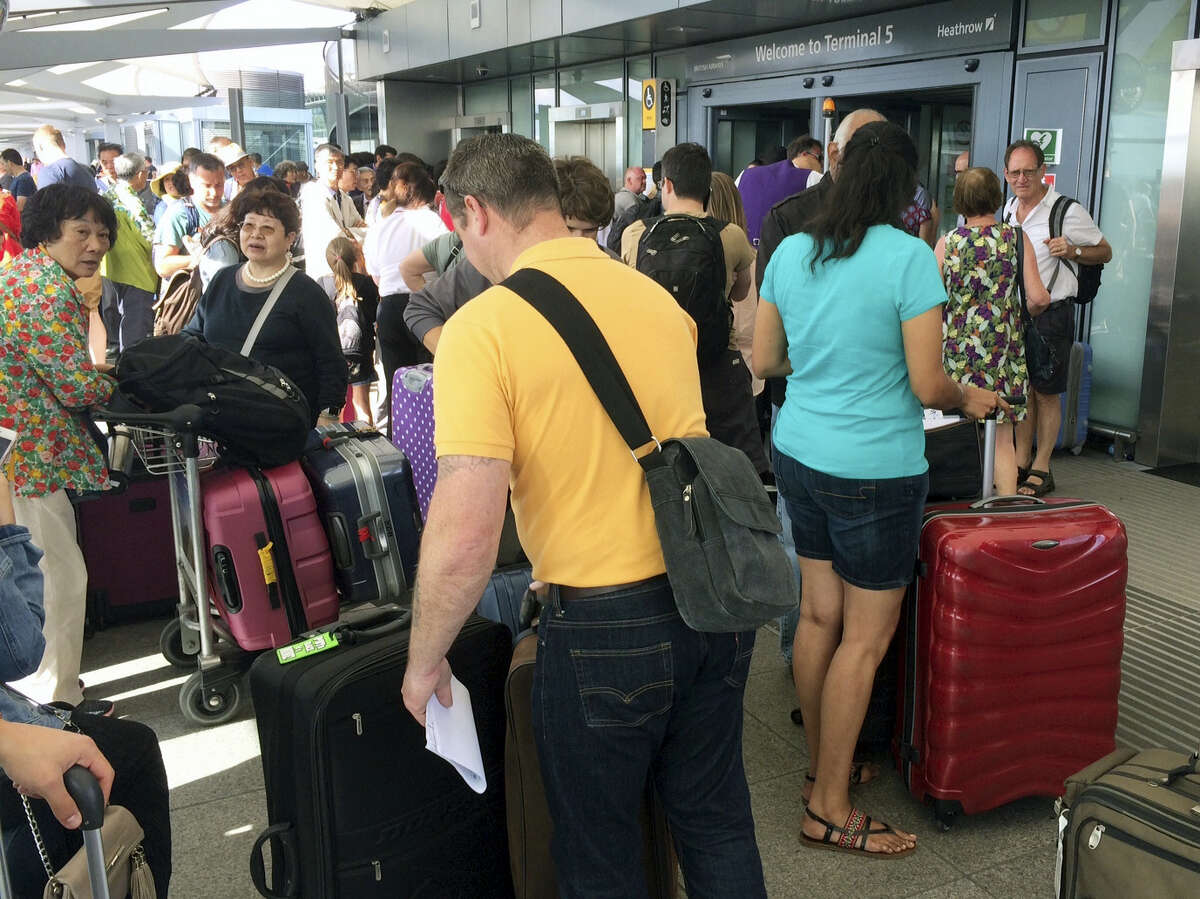 Passengers stand with their luggage outside Terminal 5 at London's Heathrow airport after flights were canceled due to the airport suffering an IT systems failure, Saturday, May 27, 2017. British Airways canceled all flights from London's Heathrow and Gatwick airports on Saturday as a global IT failure upended the travel plans of tens of thousands of people on a busy U.K. holiday weekend.