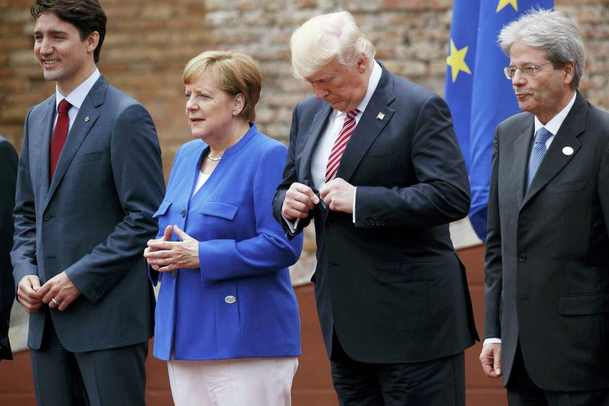 President Donald Trump adjusts his jacket during a family photo with G7 leaders at the Ancient Greek Theater of Taormina in Taormina, Italy. From left are, Canadian Prime Minister Justin Trudeau, German Chancellor Angela Merkel, Trump, and Italian Prime Minister Paolo Gentiloni.