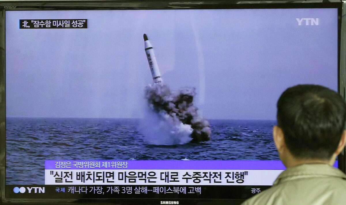 A South Korean man watches a TV news program showing an image published in North Korea's Rodong Sinmun newspaper of North Korea's ballistic missile believed to have been launched from underwater, at Seoul Railway station in Seoul, South Korea.