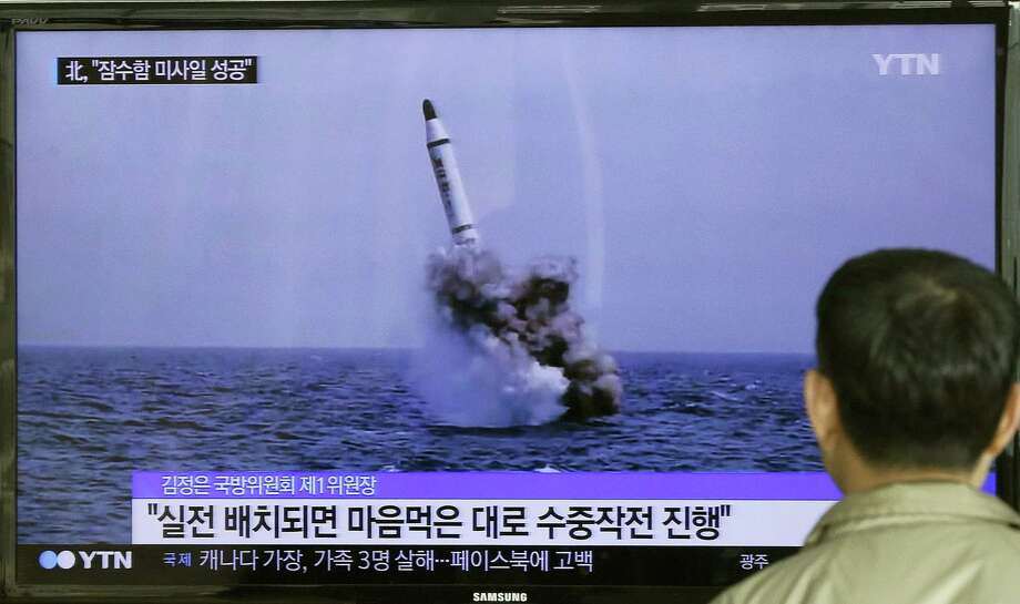 A South Korean man watches a TV news program showing an image published in North Korea's Rodong Sinmun newspaper of North Korea's ballistic missile believed to have been launched from underwater, at Seoul Railway station in Seoul, South Korea. Photo: Ahn Young-oon — The Associated Press  / AP