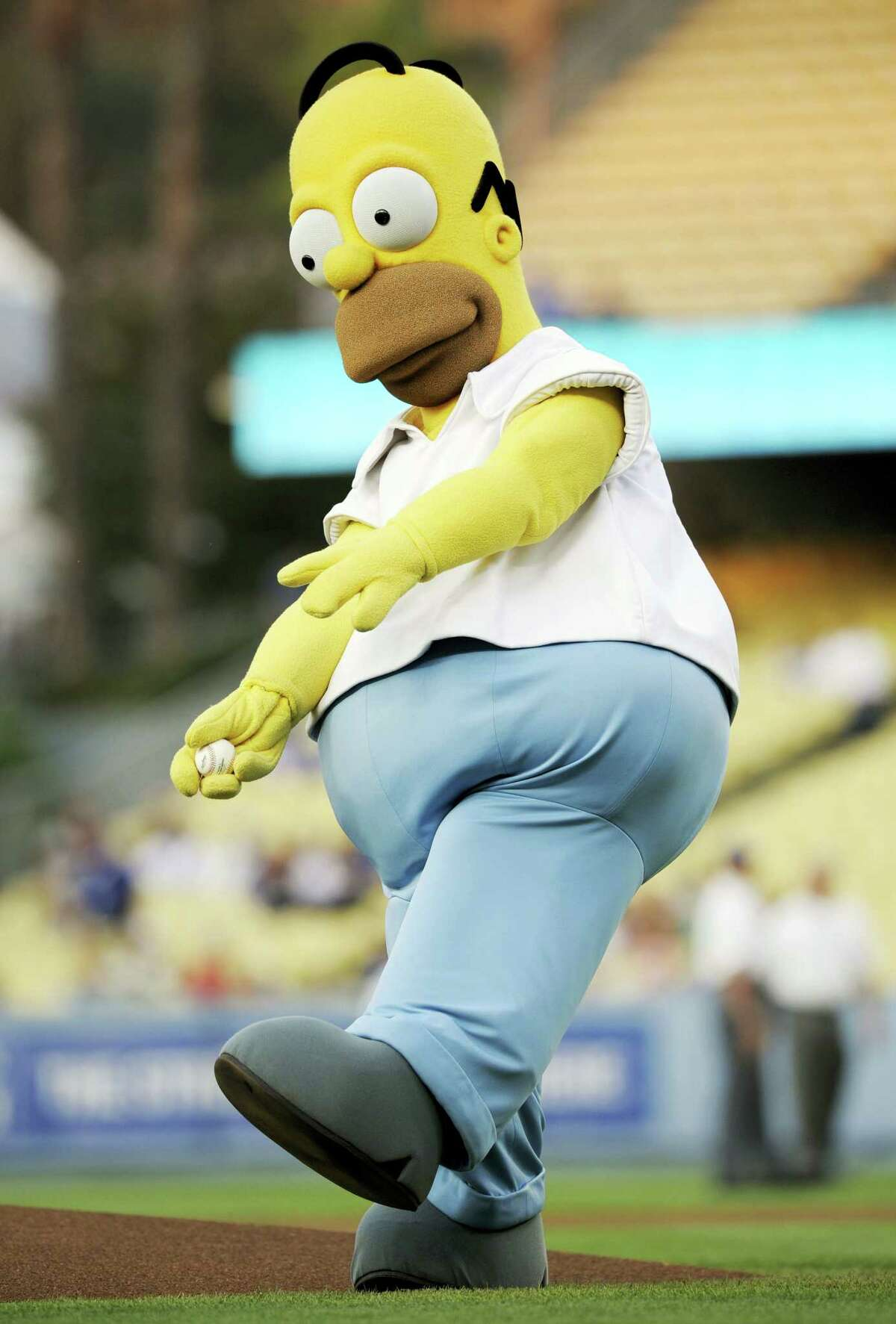 A person in a Homer Simpson costume throws the first pitch before the start of a Dodgers game.