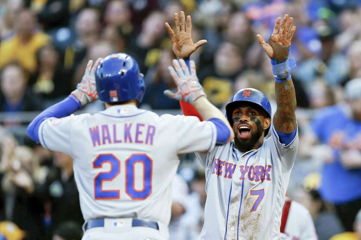 The Mets' Neil Walker (20) is greeted at home plate by Jose Reyes after hitting a two-run home run in the third inning on Friday.