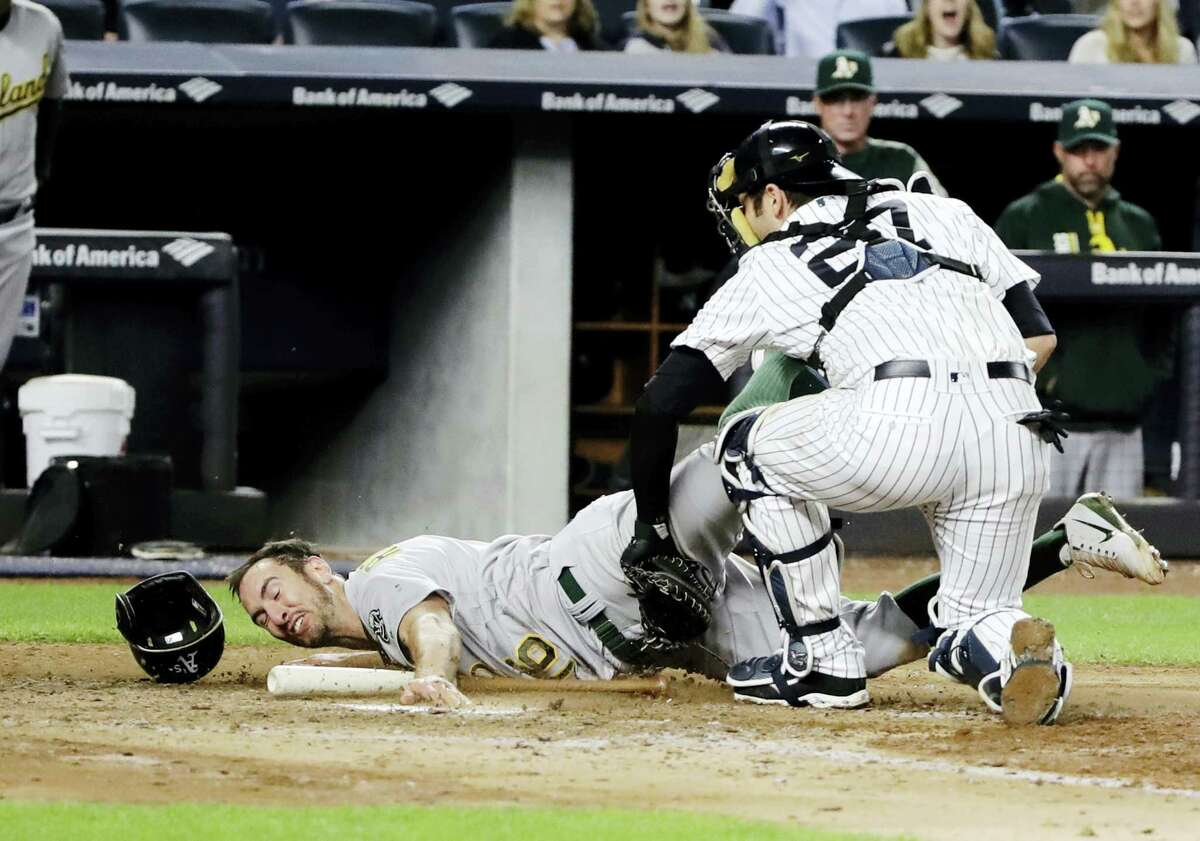 Yankees catcher Austin Romine, right, tags out the Athletics' Adam Rosales in the eighth inning Friday.