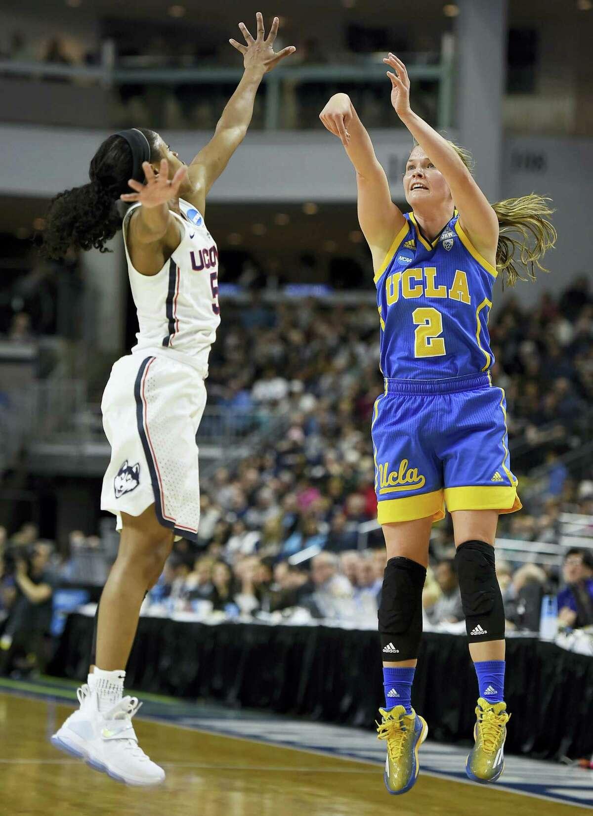 UCLA's Kari Korver follows through on 3-point basket as UConn's Crystal Dangerfield defends on Saturday.