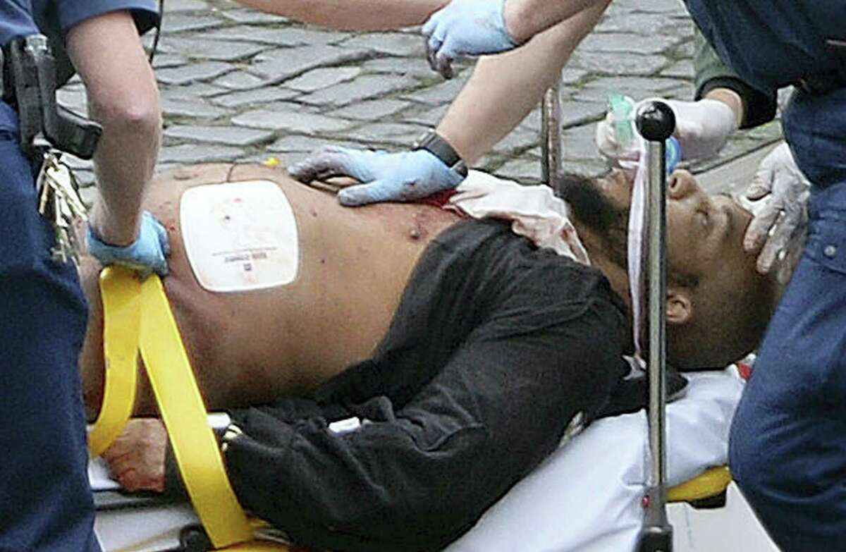 FILE- In this file photo, the attacker Khalid Masood is treated by emergency services outside the Houses of Parliament London. British Police named on Thursday Khalid Masood as The Houses of Parliament attacker.