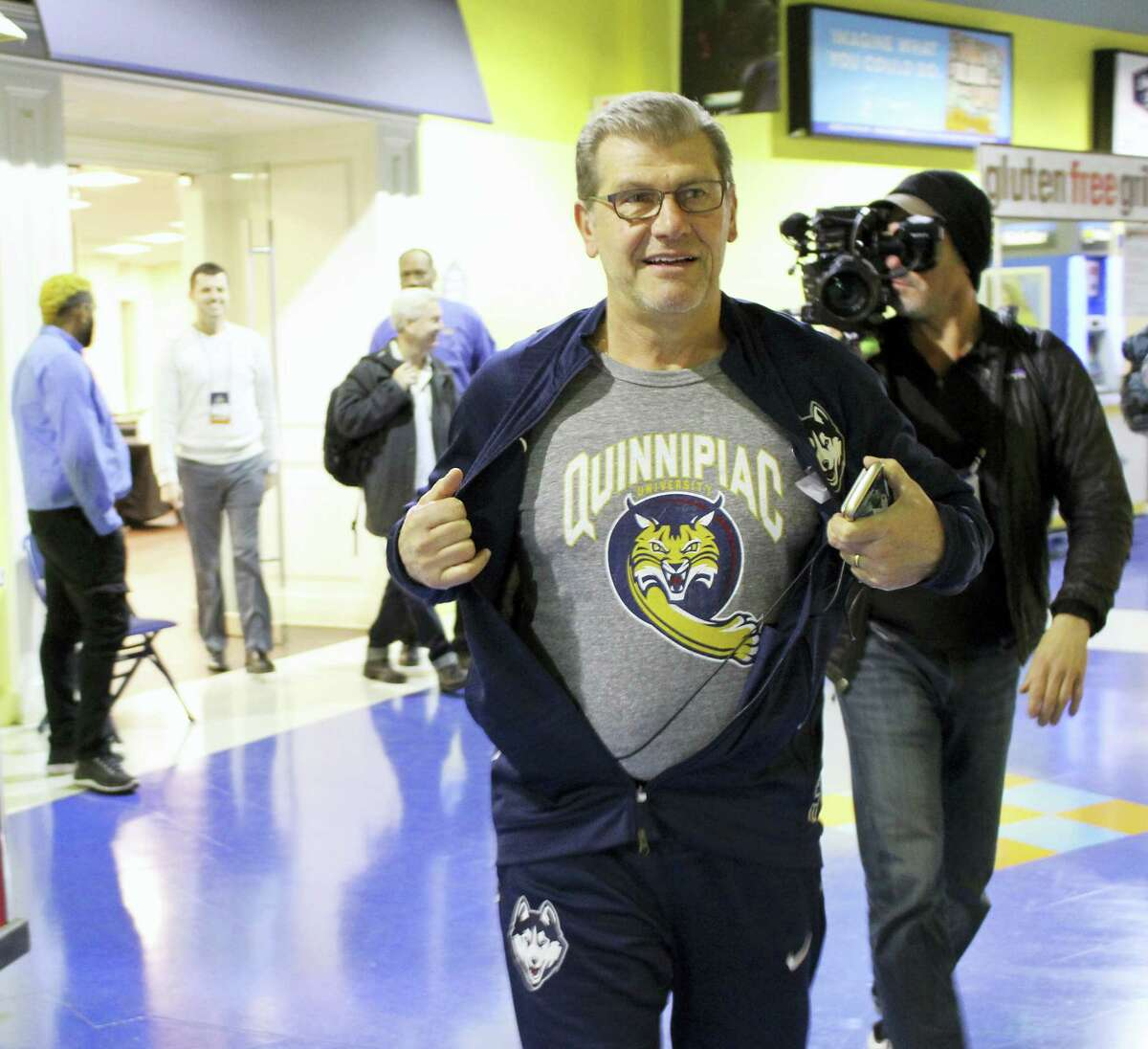 UConn coach Geno Auriemma displays a Quinnipiac University T-shirt Friday in Bridgeport. This is the first year both Connecticut schools have made it as far as the NCAA regional semifinals.
