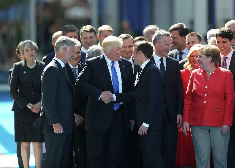 U.S. President Donald Trump, center left, shakes hands with Emmanuel Macron, France's president, as other world leaders look on during a summit of world leaders at the North Atlantic Treaty Organization (NATO) in Brussels, Belgium, on Thursday, May 25, 2017. Photo: Jasper Juinen — Bloomberg  / © 2017 Bloomberg Finance LP