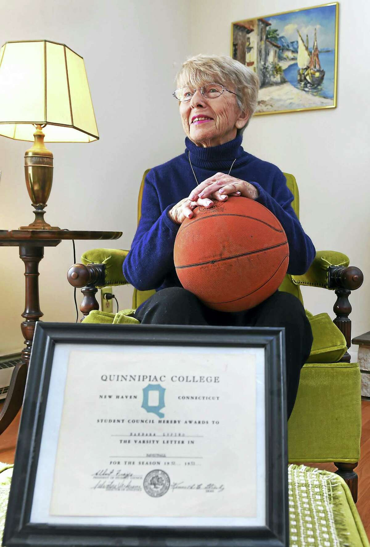 """Barbara Lupino Mecca, 83, of Hamden, sits with a certificate recognizing her as receiving a Quinnipiac College varsity letter for the schools' first women's basketball team coached by New Haven coaching legend Salvatore """"Red"""" Verderame during the 1952-1953 season."""