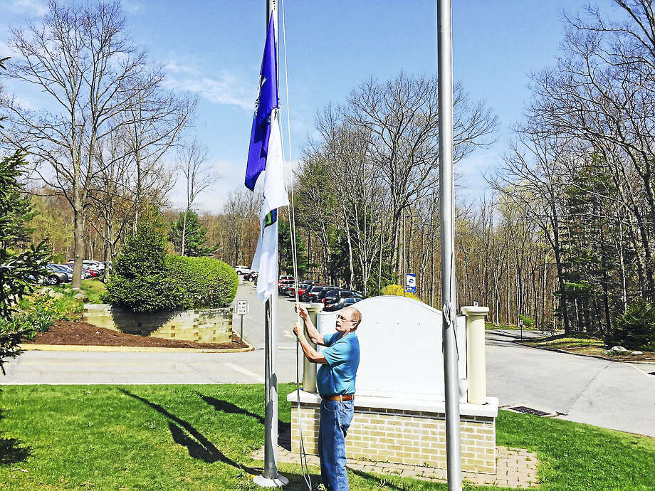 Mike Shea of Winsted raises a flag in honor of organ donation at Charlotte Hungerford Hospital. Photo: Contributed Photo
