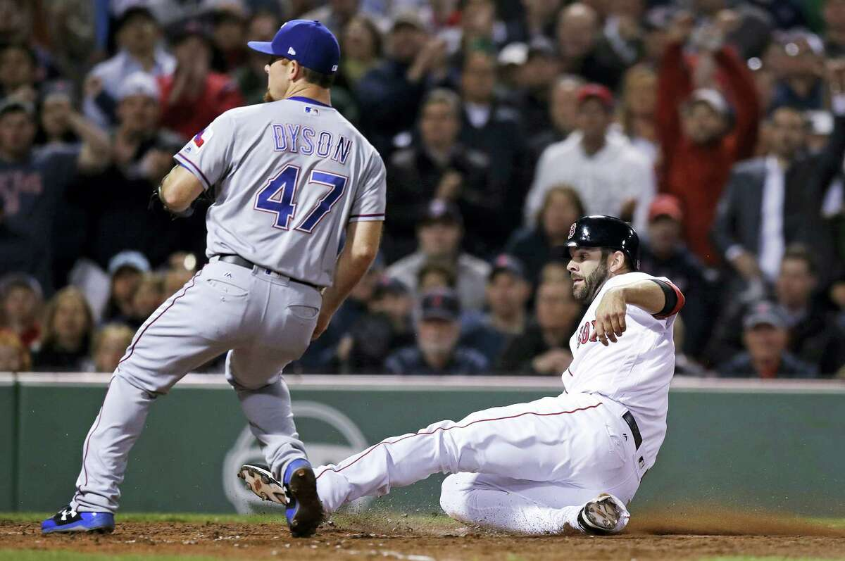 Boston Red Sox's Mitch Moreland scores on a wild pitch by Texas Rangers relief pitcher Sam Dyson (47) during the seventh inning of a baseball game at Fenway Park in Boston, Wednesday.