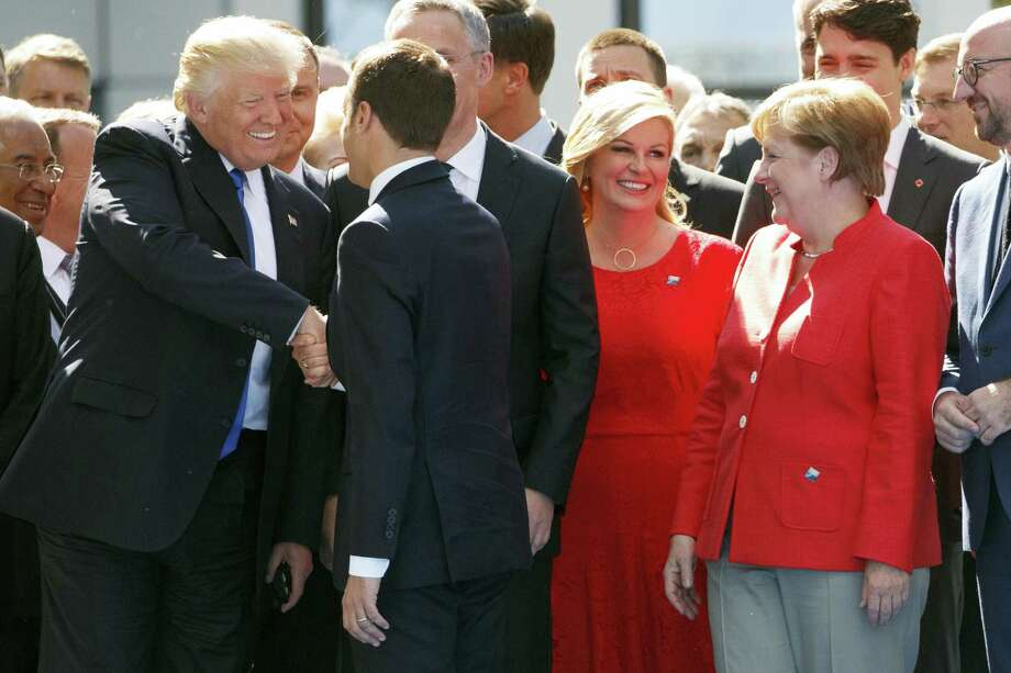 German Chancellor Angela Merkel watches at right as President Donald Trump shakes hands with French President Emmanuel Macron during a ceremony to unveil artifacts from the World Trade Center and Berlin Wall for the new NATO headquarters, Thursday, May 25, 2017, in Brussels. Photo: AP Photo/Evan Vucci  / Copyright 2017 The Associated Press. All rights reserved.