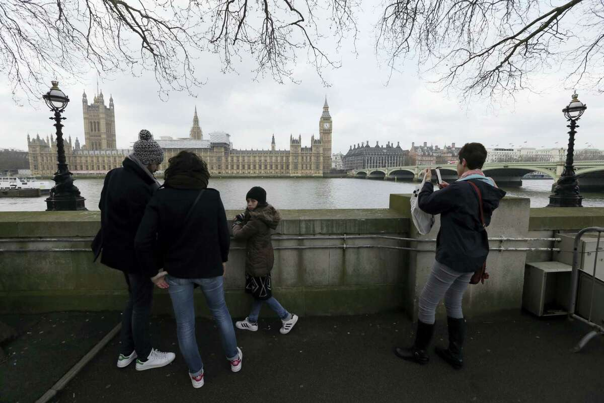 Tourists view parliament from across the River Thames, with Westminster Bridge, right, in London, Thursday March 23, 2017, the scene of an attack. On Wednesday a knife-wielding man went on a deadly rampage, first driving a car into pedestrians then stabbing a police officer to death before being fatally shot by police within Parliament's grounds in London.