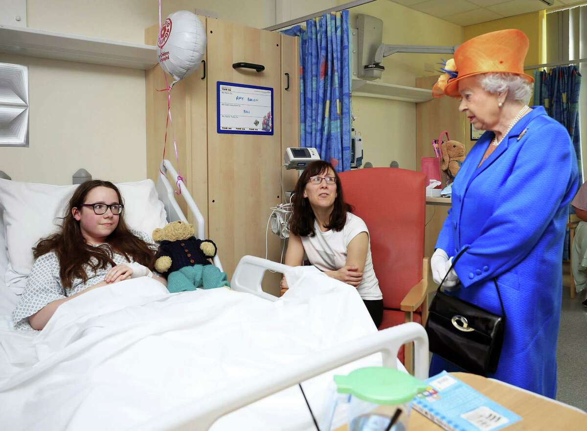 Britain's Queen Elizabeth II, right, speaks to Amy Barlow, 12, from Rawtenstall, Lancashire, left, and her mother, Kathy, as she visits the Royal Manchester Children's Hospital in Manchester England, to meet victims of the terror attack in the city earlier this week and to thank members of staff who treated them Thursday.