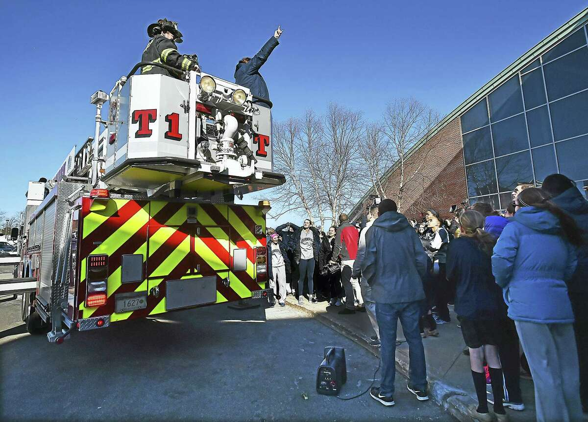 Tricia Fabbri, the head coach for the Quinnipiac women's basketball team speaks from a Hamden fire truck at the Sweet 16 Send-Off Rally for the Bobcats at the TD Bank Sports Center at the York Hill Campus in Hamden, Wednesday.