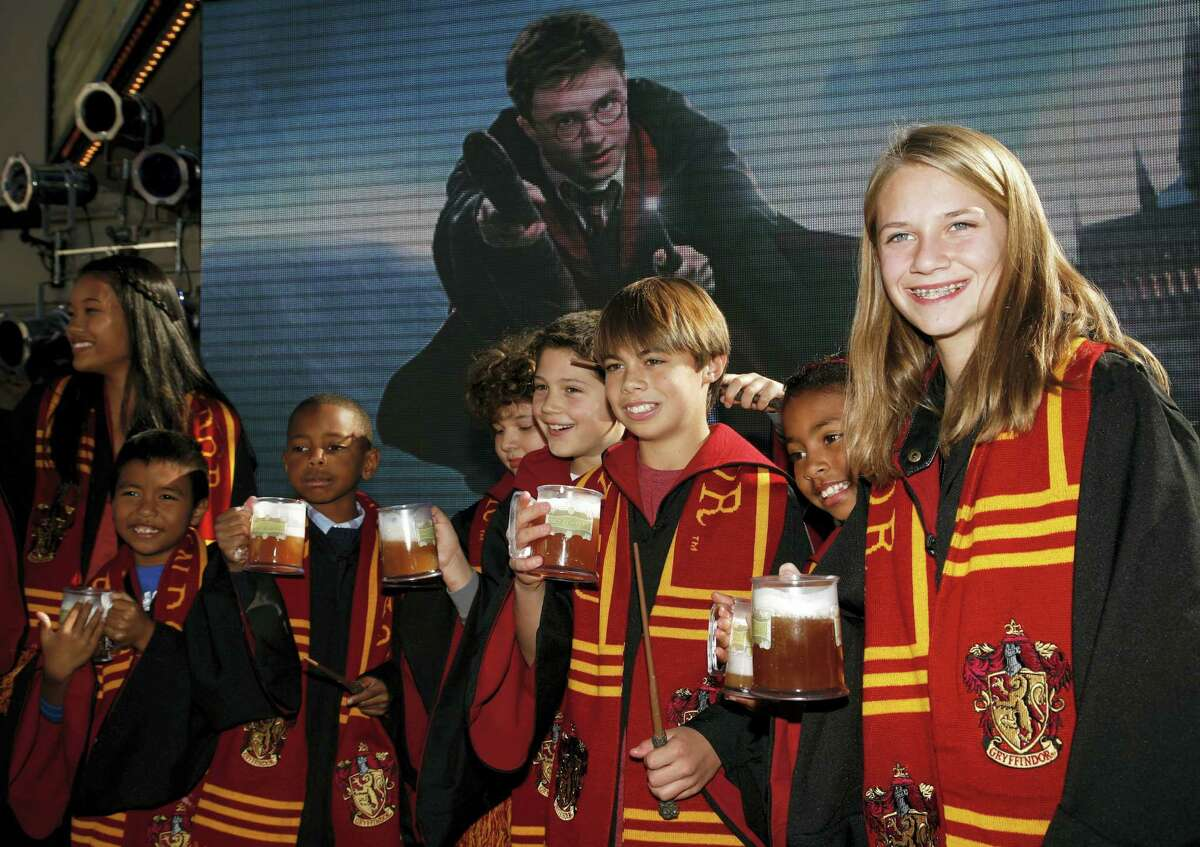 In this Dec. 6, 2011, file photo, fans dressed up as students from Hogwarts School of Witchcraft and Wizardry make a butterbeer toast as Universal Parks & Resorts announces the Harry Potter attraction is coming to Universal Studios Hollywood in Universal City, Calif. Pennsylvania's Yuengling's Ice Cream launched a new, butterbeer flavored ice cream March 20, 2017.