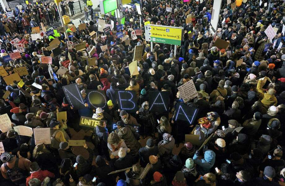 Protesters assemble at John F. Kennedy International Airport in New York, Saturday after earlier in the day two Iraqi refugees were detained while trying to enter the country. On Friday, Jan. 27, President Donald Trump signed an executive order suspending all immigration from countries with terrorism concerns for 90 days. Countries included in the ban are Iraq, Syria, Iran, Sudan, Libya, Somalia and Yemen, which are all Muslim-majority nations. Photo: Craig Ruttle — The Associated Press  / FR61802 AP