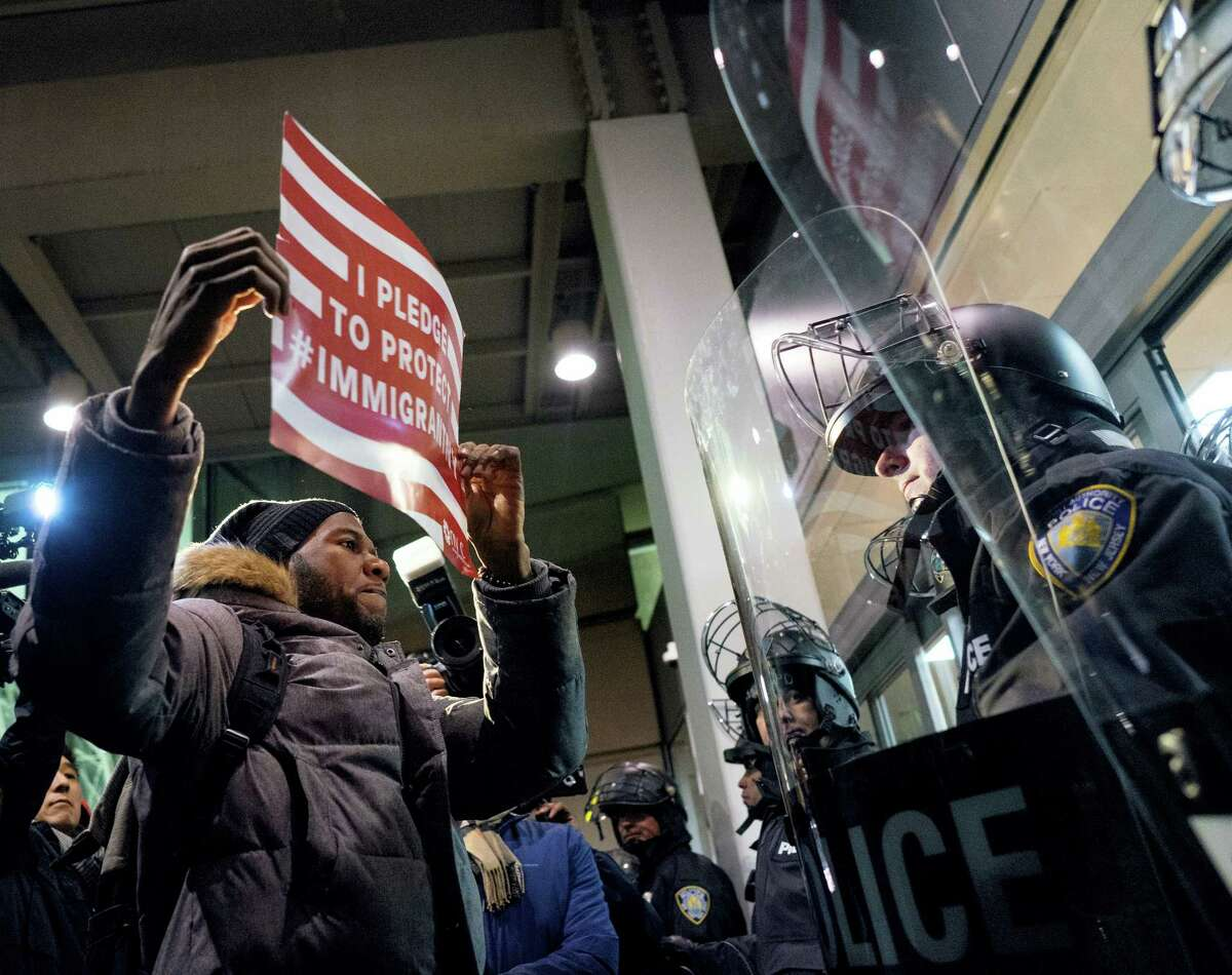 A protester stands facing police officers at an entrance of Terminal 4 at John F. Kennedy International Airport in New York, Saturday after earlier in the day two Iraqi refugees were detained while trying to enter the country. On Friday, Jan. 27, President Donald Trump signed an executive order suspending all immigration from countries with terrorism concerns for 90 days. Countries included in the ban are Iraq, Syria, Iran, Sudan, Libya, Somalia and Yemen, which are all Muslim-majority nations.