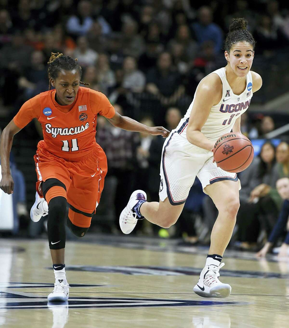 Connecticut's Kia Nurse dribbles as Syracuse's Gabby Cooper, left, defends, in the first half of a second-round game in the NCAA women's tournament Monday in Storrs.
