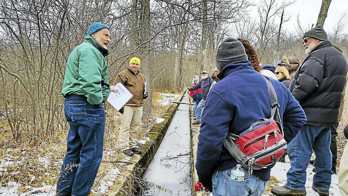 White Memorial Conservation Center research director James Fischer, center, and retired education director Jeff Greenwood, left, showed 29 visitors during a tour the canal that allowed the passage of ice blocks from Bantam Lake to the property's formerly prosperous ice house.