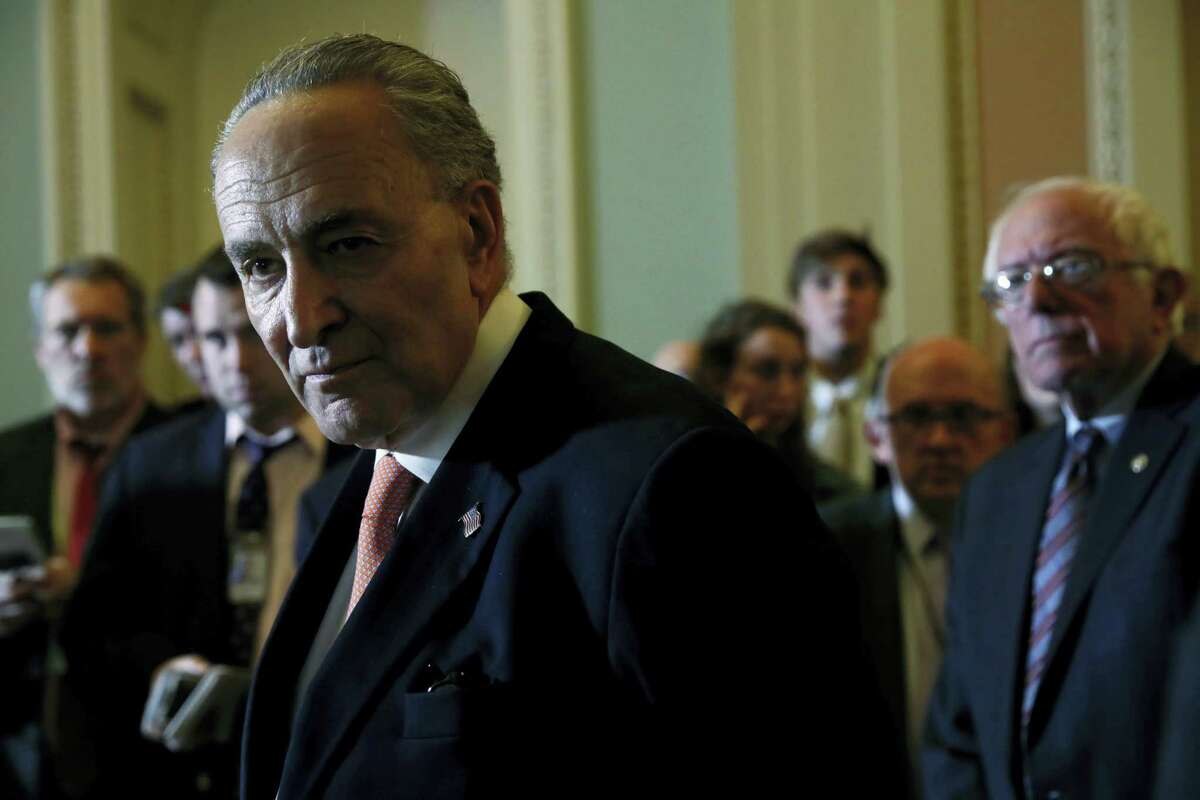 Senate Minority Leader Charles Schumer of N.Y., left, accompanied by Sen. Bernie Sanders, I-Vt., right, listens to a question during a news conference on Capitol Hill in Washington, Tuesday, may 23, 2017, following a Democratic policy luncheon.