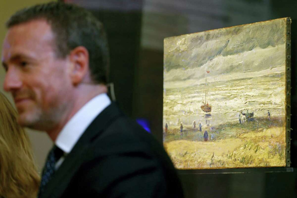 """Van Gogh Museum director Axel Rueger stands next to stolen and recovered """"Seascape at Scheveningen"""" by Dutch master Vincent van Gogh, during a press conference in Amsterdam, Netherlands, Tuesday, March 21, 2017. Two paintings by Vincent van Gogh titled """"Seascape at Scheveningen"""" (1882) and """"Congregation leaving the Reformed Church in Nuenen,"""" (1884-1885) returned to the Amsterdam museum after they were stolen from in a nighttime heist 15 years ago and recovered by Naples police in Italy. (AP Photo/Peter Dejong)"""