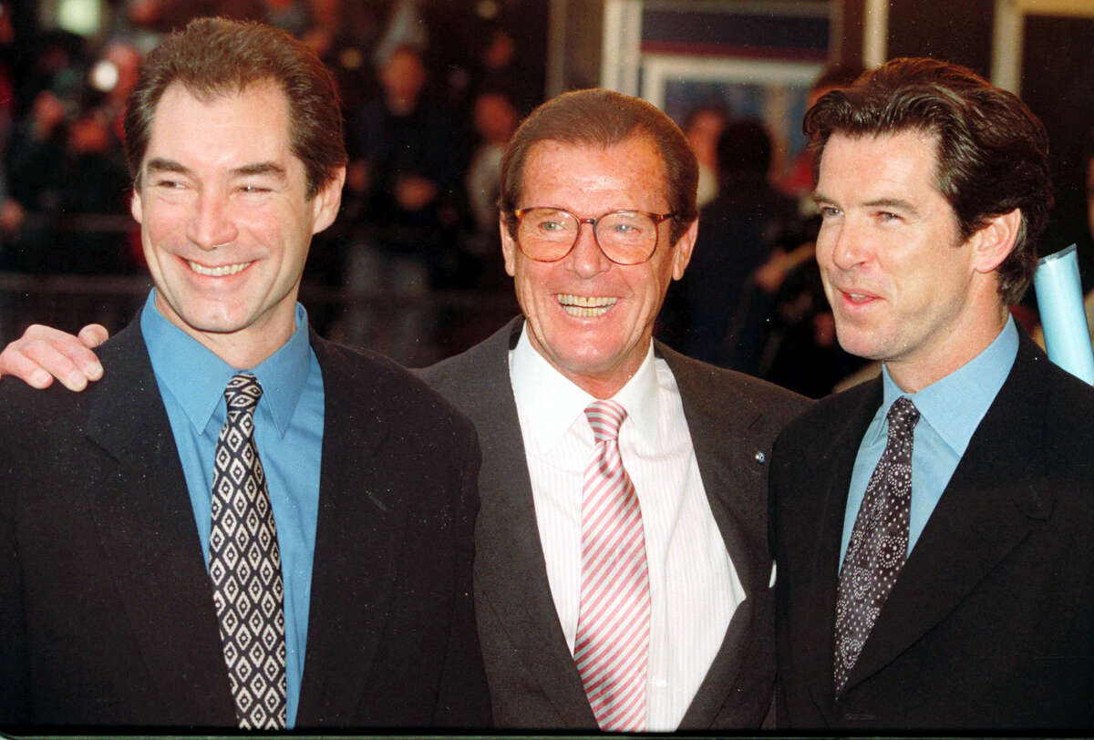 """In this Sunday, Nov. 17, 1996, file photo, three of the actors who played James Bond, Timothy Dalton left, Roger Moore, center, and Pierce Brosnan, at a London cinema to celebrate the life of Albert R. """"Cubby"""" Broccoli, the American film producer behind seventeen Bond movies. In total, six actors have portrayed Bond officially. The upcoming """"Spectre"""" with Daniel Craig as 007 is the 24th in the series. Roger Moore's family said Tuesday May 23, 2017 that the former James Bond star has died after a short battle with cancer."""