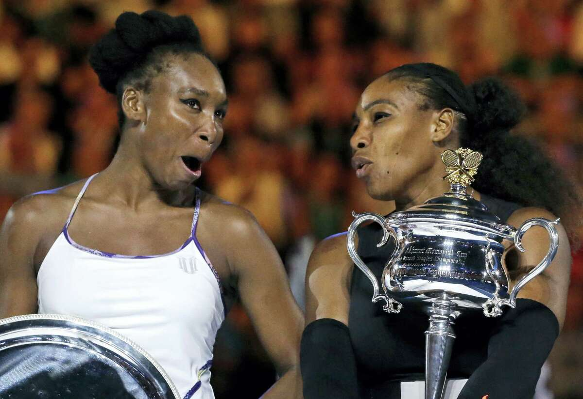 United States' Serena Williams, right, and her sister, Venus, chat, holding their trophies after Serena won the women's singles final at the Australian Open tennis championships in Melbourne, Australia, Saturday, Jan. 28, 2017.