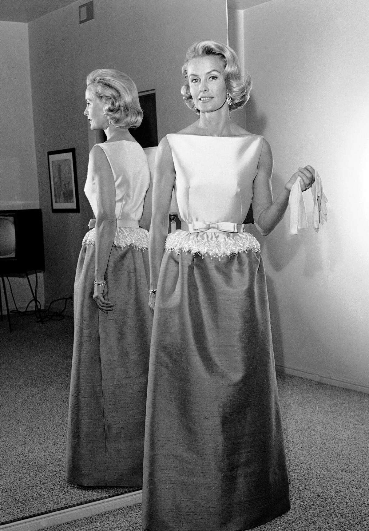 In this April 6, 1962, file photo, socialite-actress Dina Merrill models the gown she will wear at the Academy Awards presentation in Los Angeles. Merrill, the rebellious heiress who defied her super-rich parents to become an actress, died Monday, May 22, 2017, at age 93.