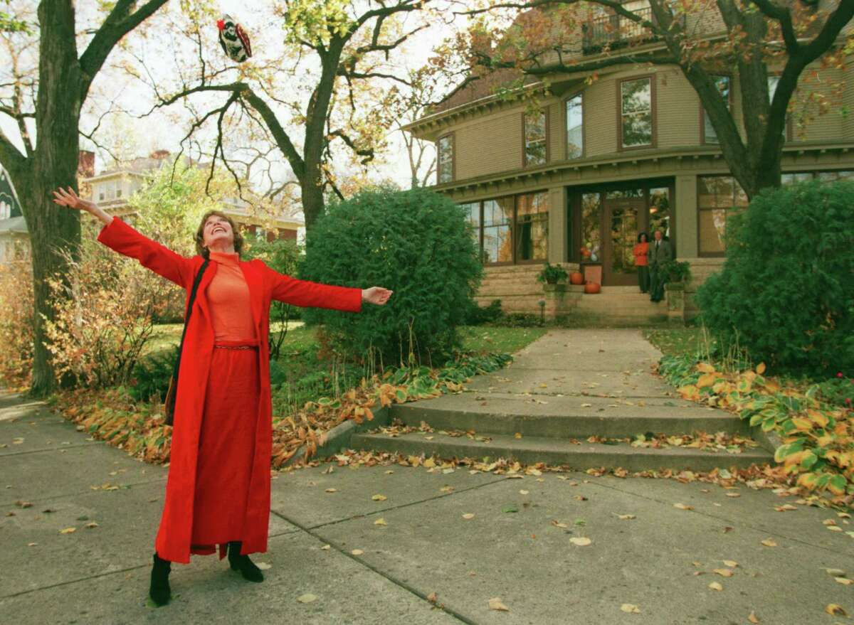 """This photo taken in 1996 shows Mary Tyler Moore tossing her hat up as she revisits the Minneapolis Kenwood neighborhood house which was her television """"home"""" for the television show The Mary Tyler Moore Show some 25 years earlier."""