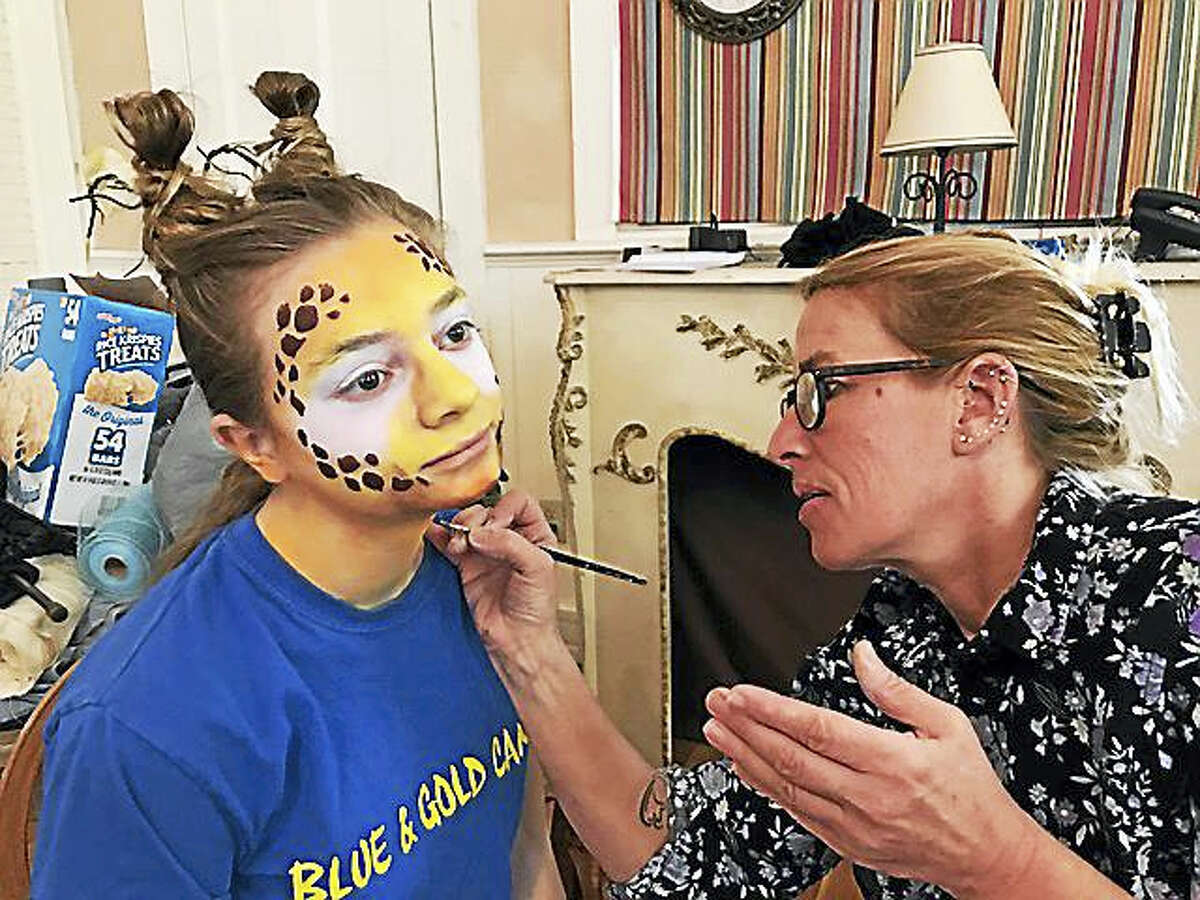 """Artist Beth Miller paints Maguerite Bickford's face in preparation for """"Madagascar,"""" which is being presented by Falls Village Children's Theater March 31-April 2."""