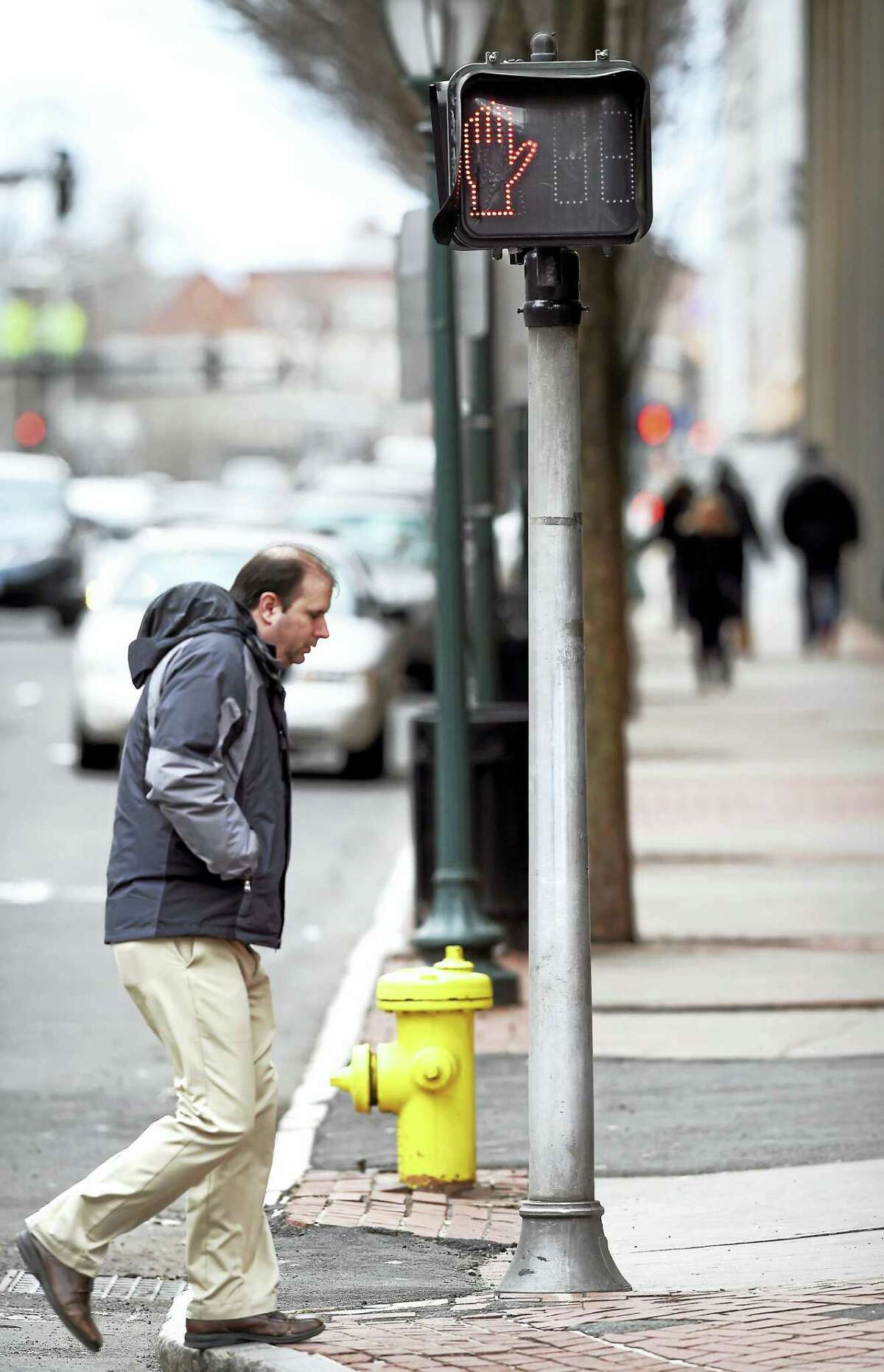 A pedestrian crosses the intersection of Church Street and Chapel Street in New Haven.