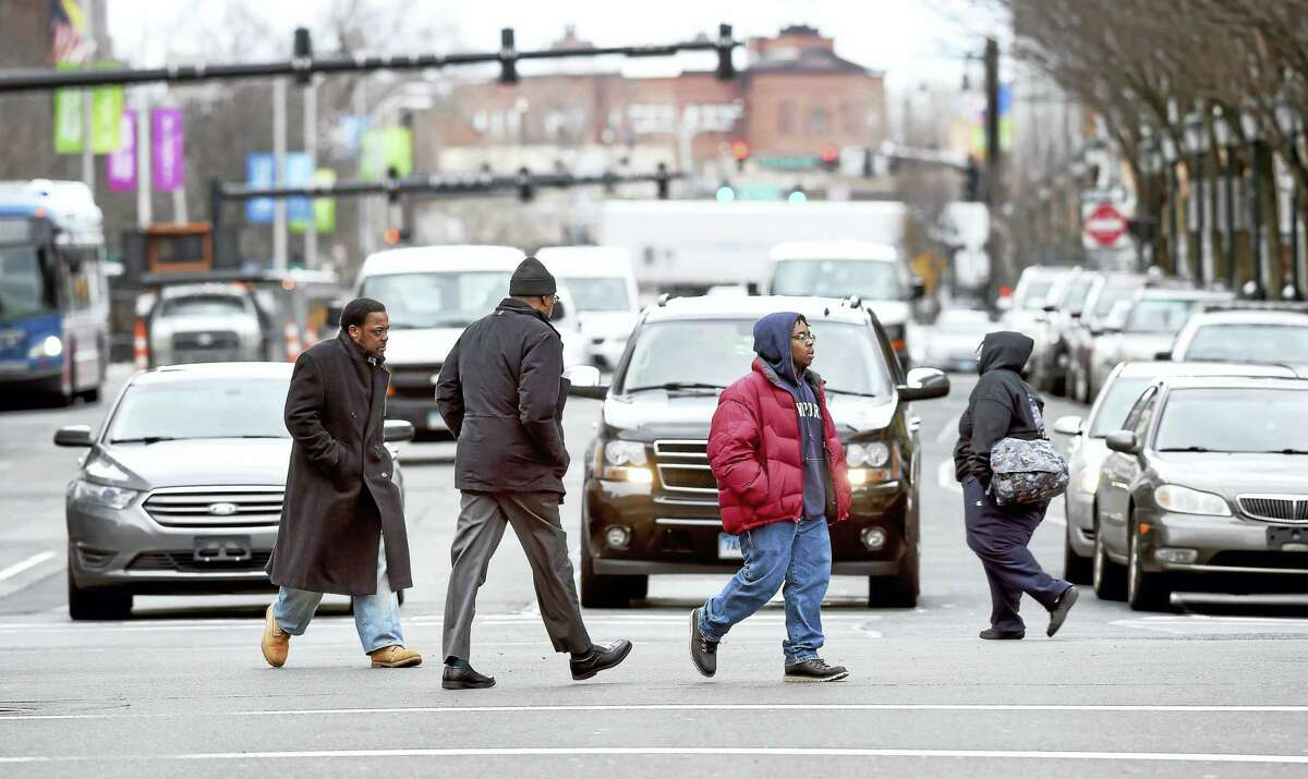 Pedestrians cross the intersection of Church Street and Chapel Street in New Haven.