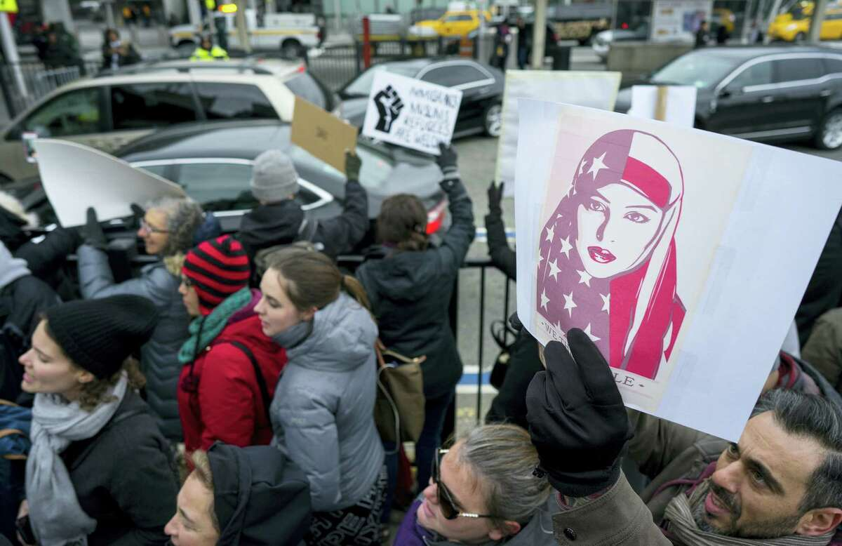 Protesters assemble at John F. Kennedy International Airport in New York on Saturday after two Iraqi refugees were detained while trying to enter the country.