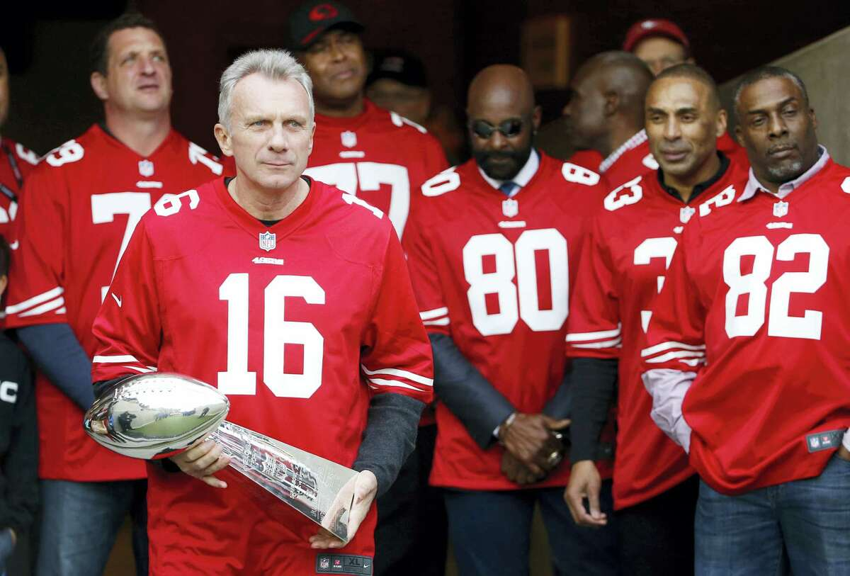 Former 49ers quarterback Joe Montana (16) carries the Super Bowl trophy as he and other former players are introduced for a halftime ceremony in Santa Clara.