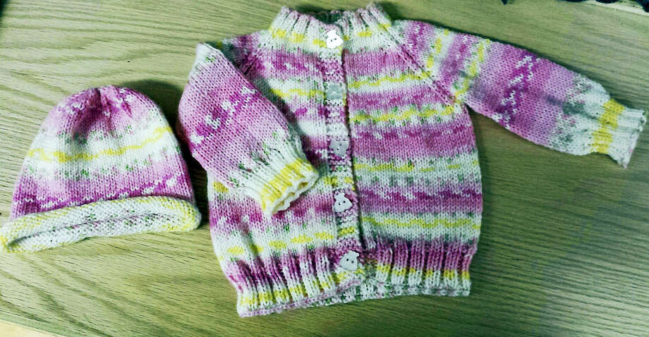 A charming baby sweater and matching hat, created by Kathy Botass. Photo: Contributed Photo By Ginger Balch